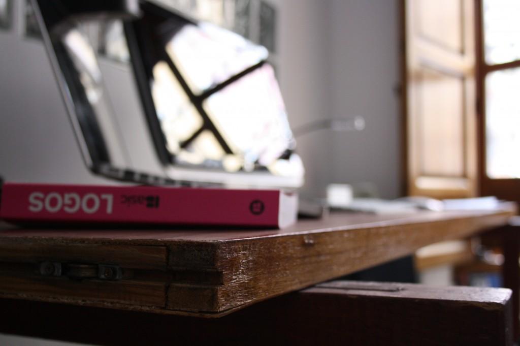 Puerta de armario como mesa, libro de logos, MacBookPro y monitr